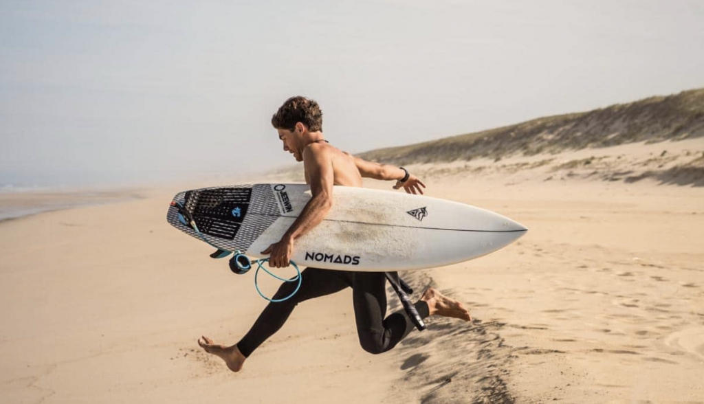 Homme qui court avec une planche de surf nomade surfing